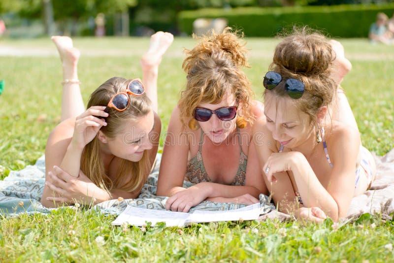 Jovem mulher três na praia que lê um compartimento imagens de stock royalty free
