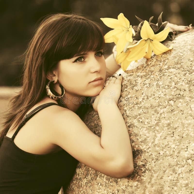 Jovem mulher triste com flores na rua da cidade imagens de stock