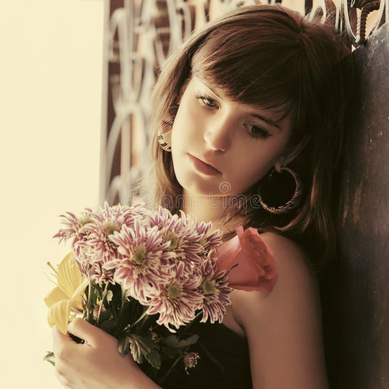 Jovem mulher triste com flores na rua da cidade foto de stock