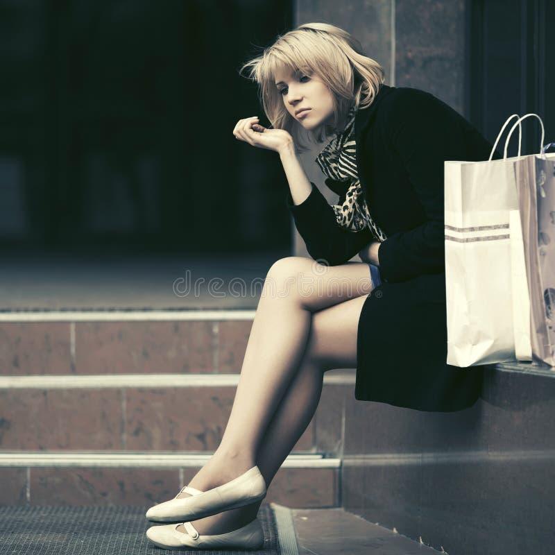 A jovem mulher triste com os sacos de compras que sentam-se na alameda pisa imagem de stock