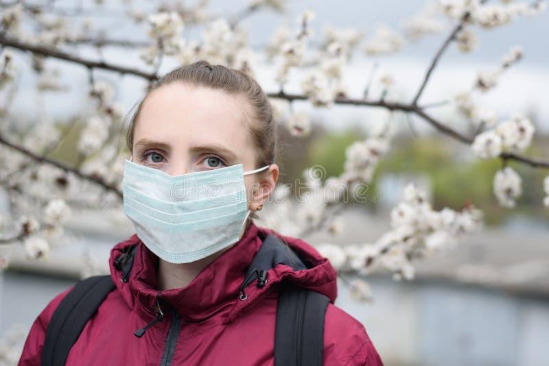 Jovem mulher triste na máscara protetora médica protetora ?rvore de floresc?ncia no fundo Alergia da mola imagem de stock royalty free