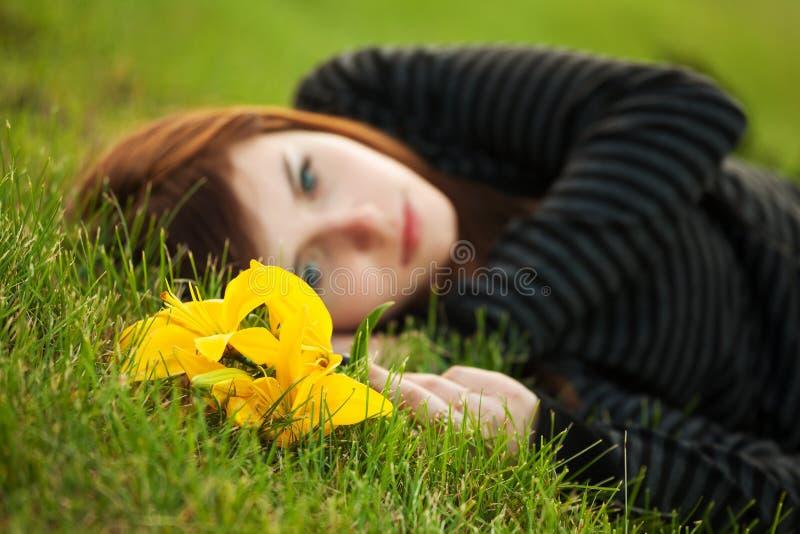 Jovem mulher triste que encontra-se na grama imagem de stock royalty free