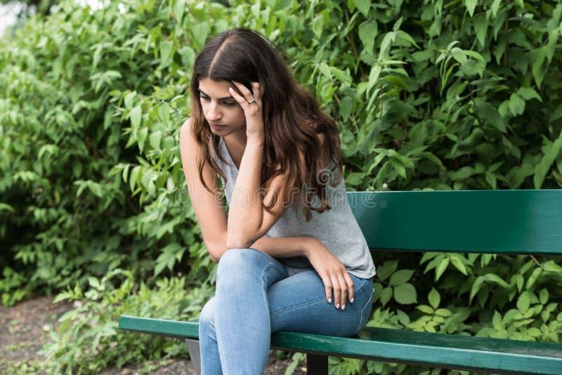 Jovem mulher triste que senta-se no banco fotos de stock royalty free