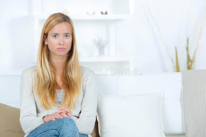 Jovem mulher triste que senta-se pelo sofá em casa imagem de stock