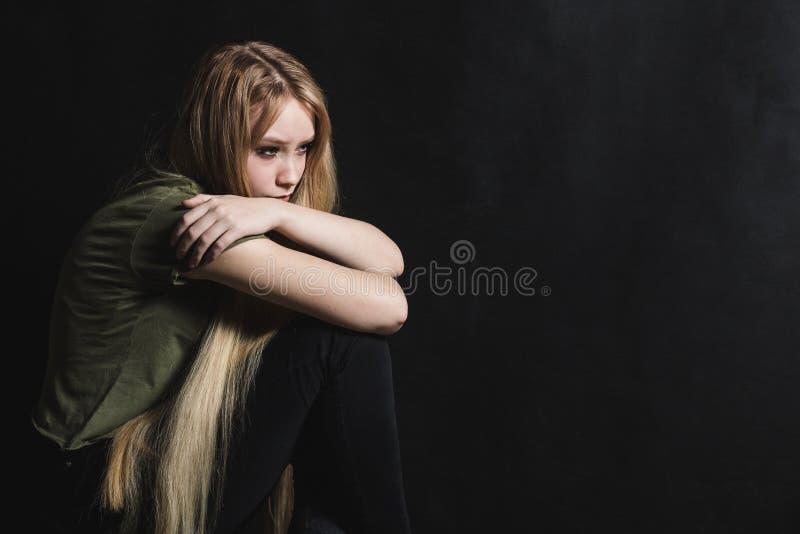 Jovem mulher triste que vai gritar em um fundo preto fotos de stock