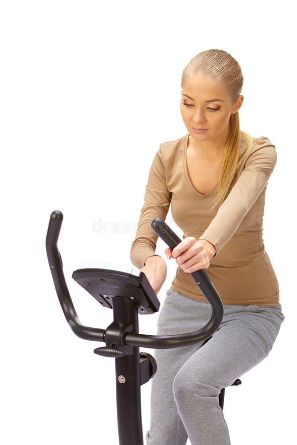 A jovem mulher usa o instrutor estacionário da bicicleta imagens de stock