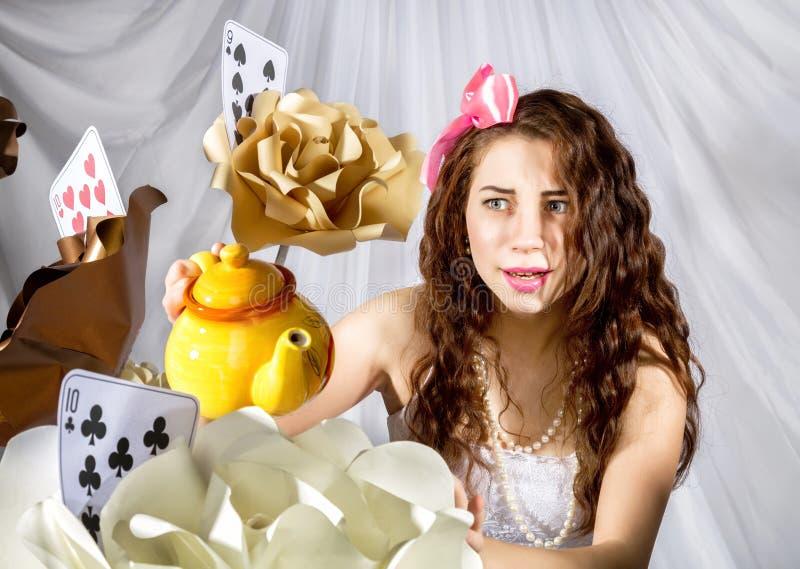 Jovem mulher vestida como Alice no país das maravilhas com chaleira e as flores grandes fotos de stock