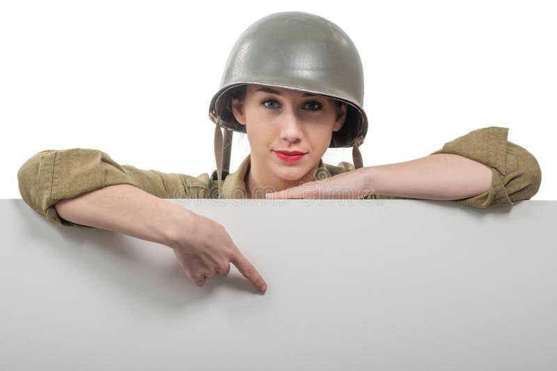 Jovem mulher vestida no uniforme militar do americano ww2 que mostra o quadro indicador vazio vazio imagens de stock
