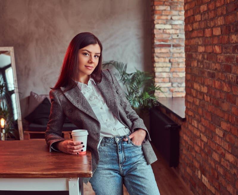A jovem mulher vestiu-se em um revestimento elegante cinzento que guarda o copo do café afastado ao inclinar-se em uma tabela em  imagem de stock