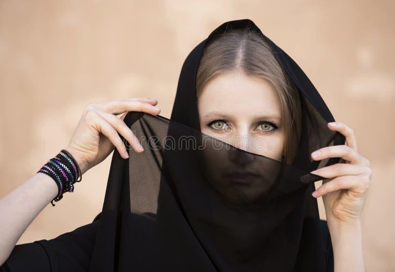 A jovem mulher vestiu-se no vestido tradicional do emirati em um deserto imagem de stock