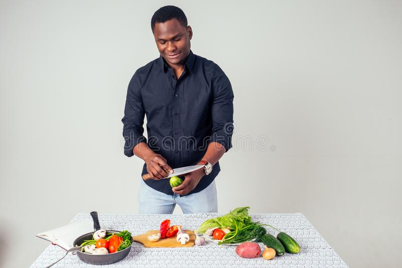 Jovem negro cozinhando em casa na cozinha doméstica e preparando uma refeição vegetariana alimento vegetativo em fundo branco imagens de stock royalty free