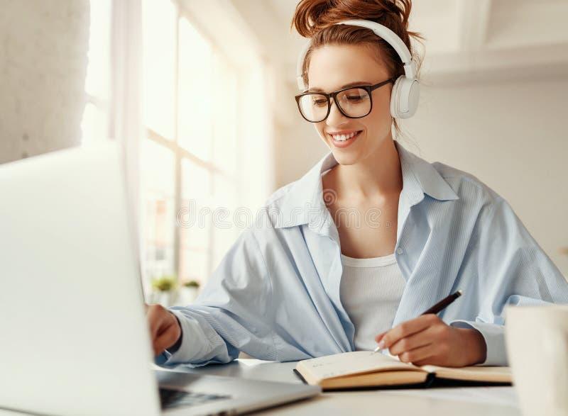 Jovem satisfeita com fones de ouvido usando laptop em casa fotografia de stock royalty free