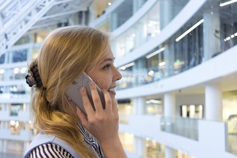 Jovem senhora alegre que est? perto da parede de vidro do shopping que fala pelo telefone Moça blondy bonita que chama com espert fotos de stock royalty free