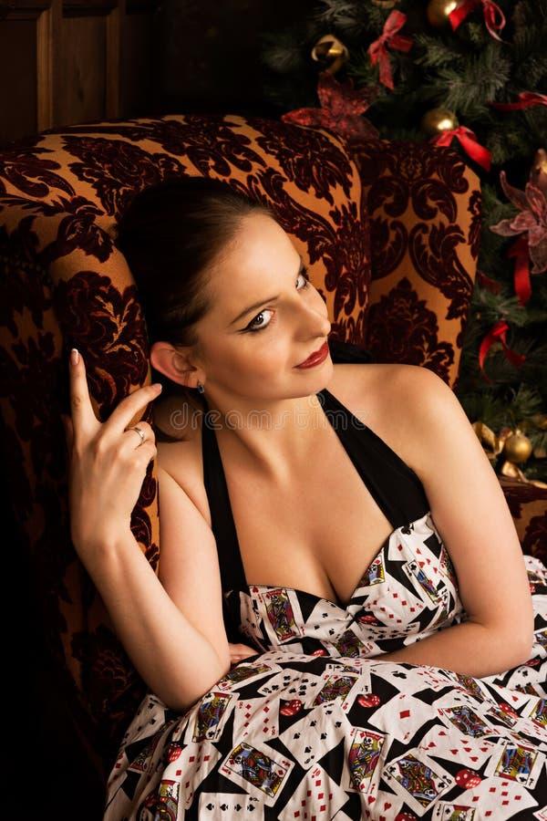 Jovem senhora alegre que senta-se perto da árvore de Natal imagens de stock royalty free