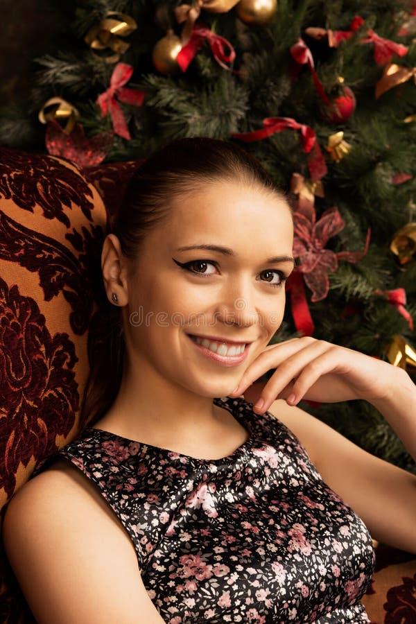 Jovem senhora alegre que senta-se perto da árvore de Natal imagem de stock royalty free