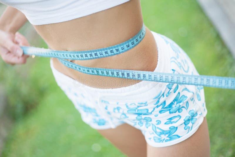 Jovem senhora apta e saudável que mede sua cintura com um measu da fita imagem de stock royalty free