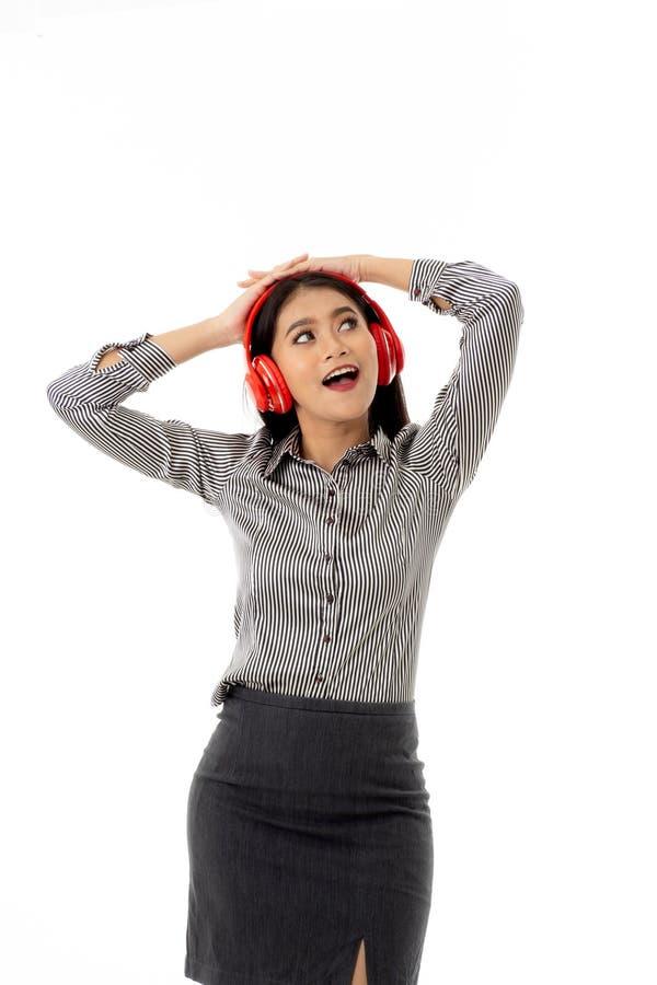 Jovem senhora asiática de sorriso bonita que veste fones de ouvido vermelhos em gestos alegres, esticando seus braços e para olha fotografia de stock