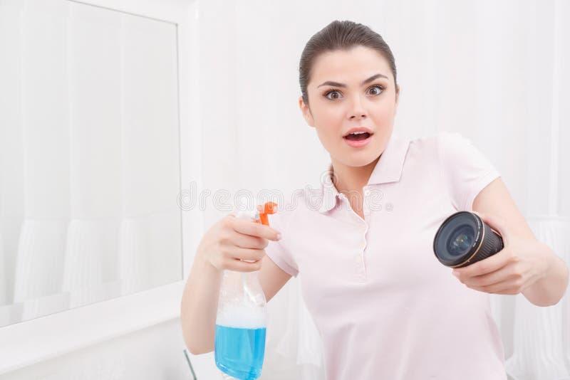 A jovem senhora atua como o objeto-vidro de limpeza imagem de stock