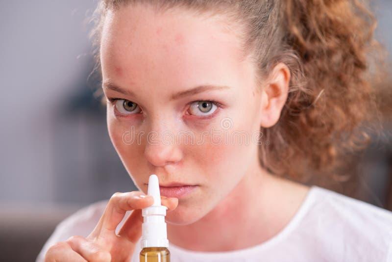 Jovem senhora bonita com claro - olhos verdes que pulverizam a medicina fotos de stock royalty free