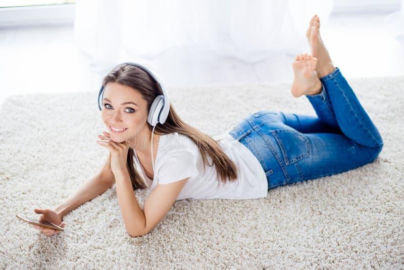 A jovem senhora bonita está escutando a música com os fones de ouvido em h foto de stock
