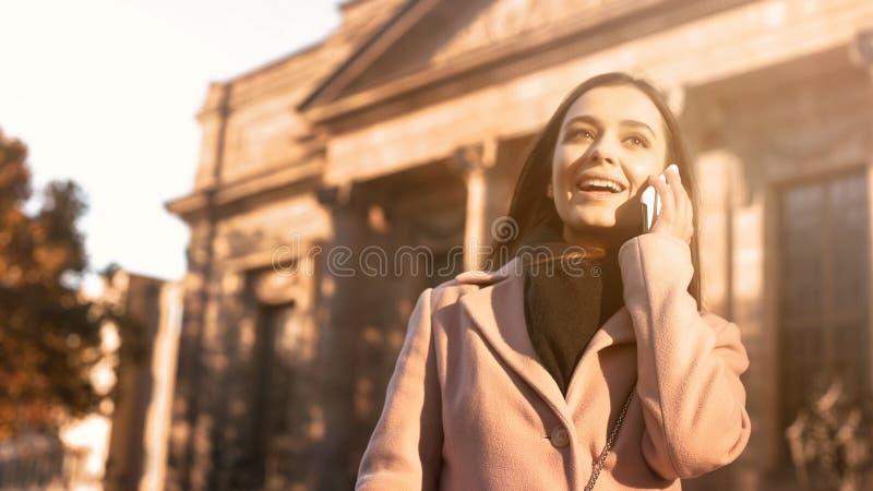 Jovem senhora bonita que fala no smartphone, estando perto da constru??o cl?ssica imagens de stock royalty free