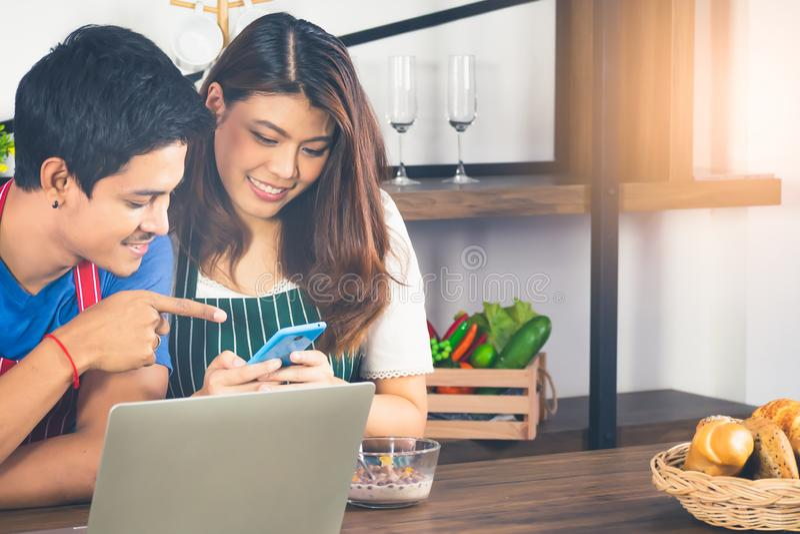 Jovem senhora bonita que olha o smartphone com seu noivo Pares asiáticos que fazem a compra em linha junto no fim de semana novo fotos de stock royalty free