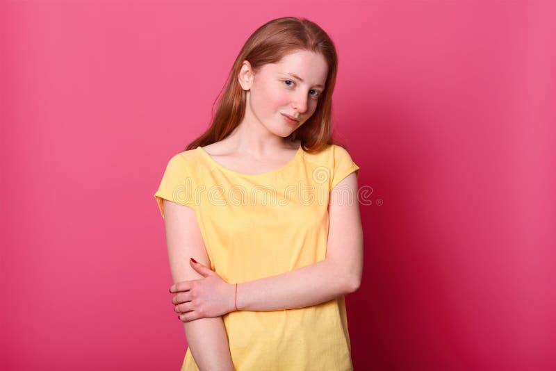 A jovem senhora bonita romântica que olha diretamente na câmera, tem a expressão facial tímida, levantando sobre o fundo cor-de-r fotografia de stock