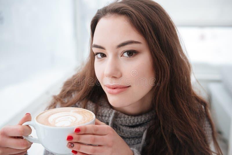 Jovem senhora bonita vestida no café bebendo da camiseta fotografia de stock royalty free
