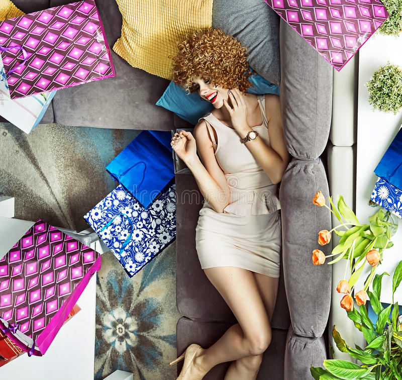 Jovem senhora com muitos sacos de compras que encontram-se no sofá foto de stock royalty free