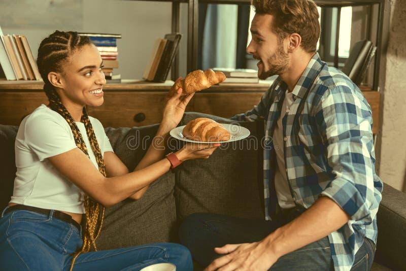 Jovem senhora consciente que trata o soulmate com a pastelaria saboroso imagens de stock royalty free