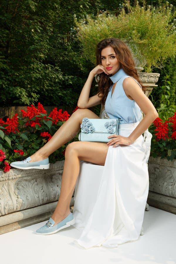 A jovem senhora elegante, fino e à moda com composição e penteado está levantando perto da mansão bonita fotos de stock