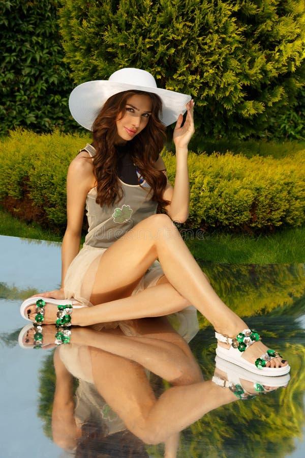 A jovem senhora elegante, impressionante e à moda está levantando no parque natural, no gramado verde, na grama e na folha no fun foto de stock
