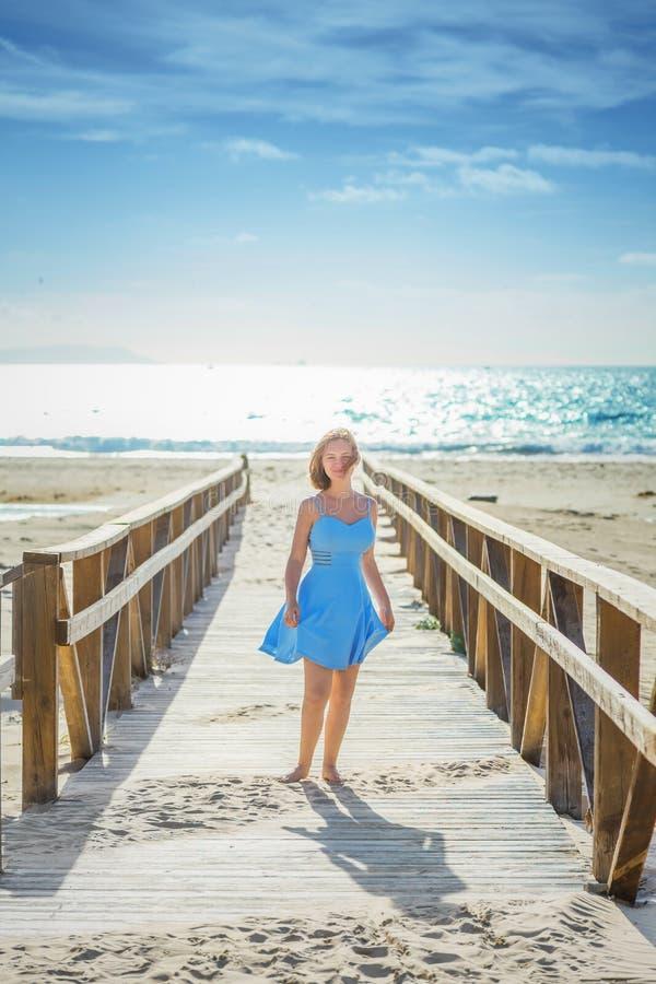 Jovem senhora em sundress dos azul-céu na ponte de madeira fotografia de stock