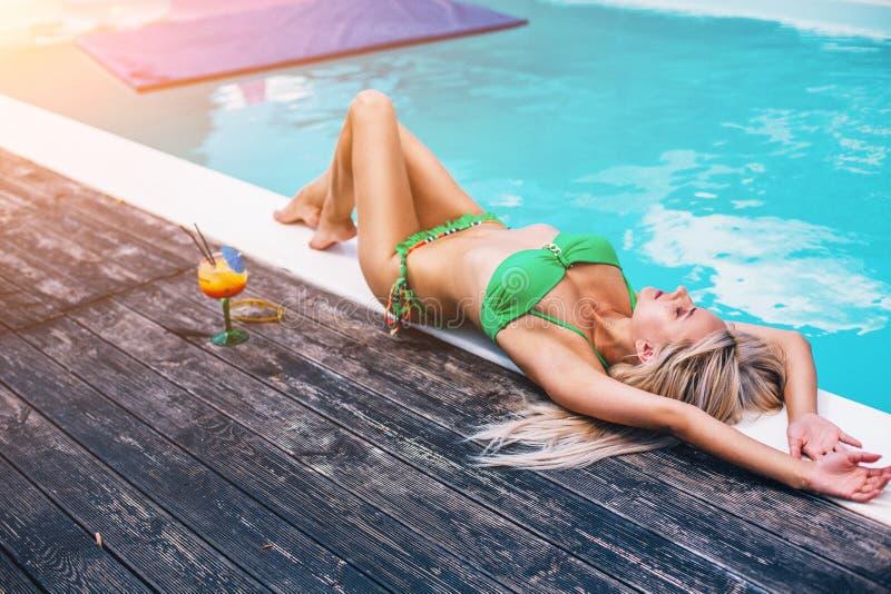 A jovem senhora In Green Bikini est? colocando perto da associa??o e de tomar sol de Sweemimng fotografia de stock