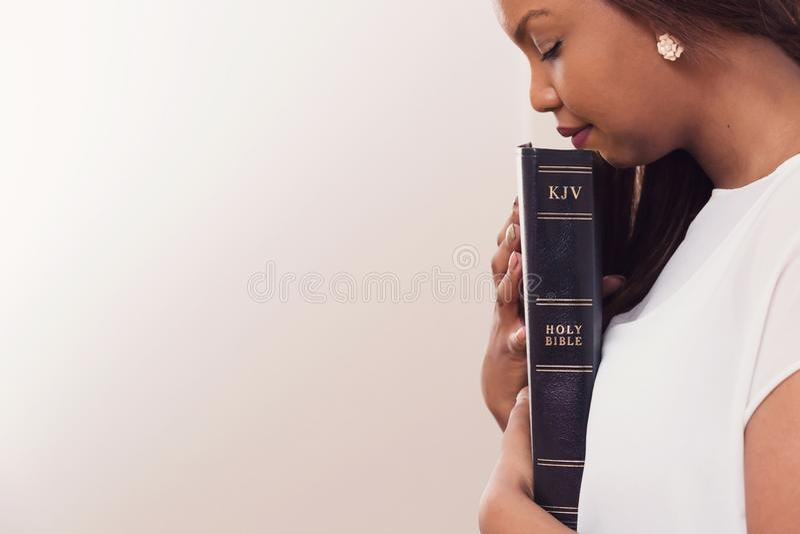 Jovem senhora Holding Her Bible perto de seu coração fotografia de stock