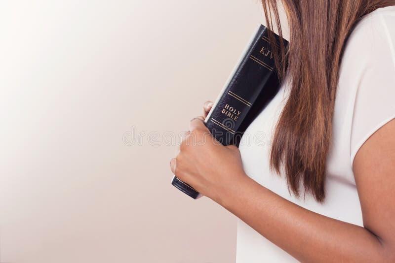 Jovem senhora Holding Her Bible perto de seu coração imagens de stock royalty free