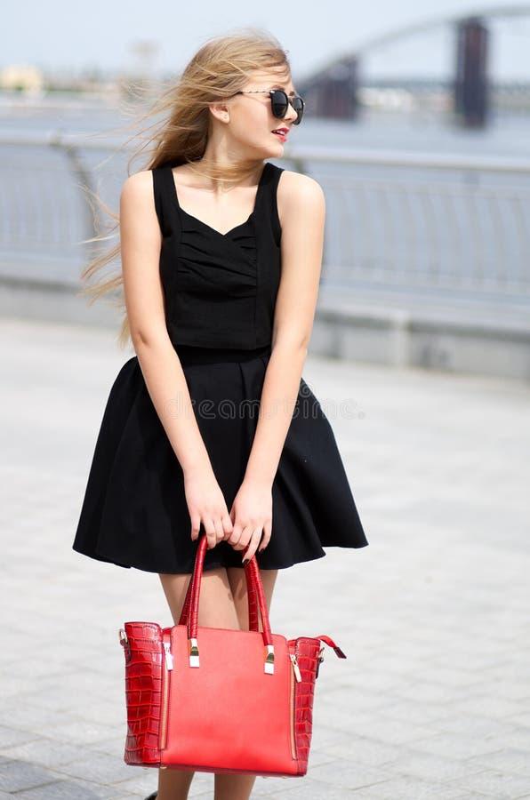 A jovem senhora na saia preta, a camisa sem mangas e a forma ensacam o posi fotografia de stock