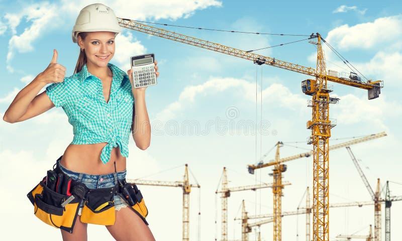 Jovem senhora no capacete de segurança que guarda a calculadora foto de stock royalty free