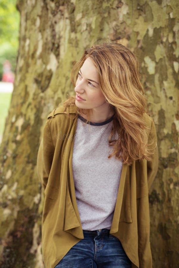 Jovem senhora pensativa no tronco de árvore que olha acima foto de stock royalty free