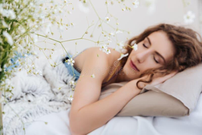 Jovem senhora que dorme dentro na cama Olhos fechados foto de stock royalty free