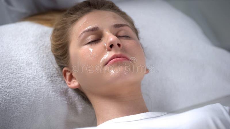 Jovem senhora que relaxa no salão de beleza da cosmetologia com máscara da anti-idade em sua cara foto de stock