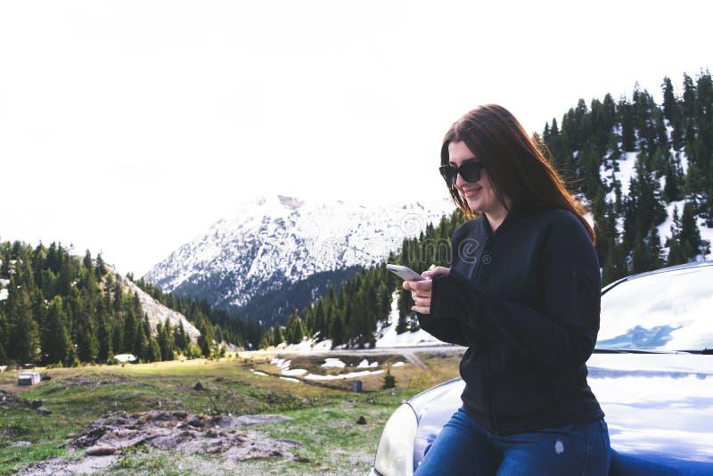 jovem senhora que senta-se em uma capota de um carro usando o telefone esperto nas montanhas Menina feliz que envia a mensagem co fotografia de stock royalty free
