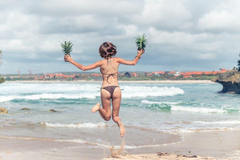 Jovem senhora 'sexy' no biquini que salta na praia com fruto saudável cru fresco do abacaxi Conceito feliz das férias bali imagens de stock royalty free