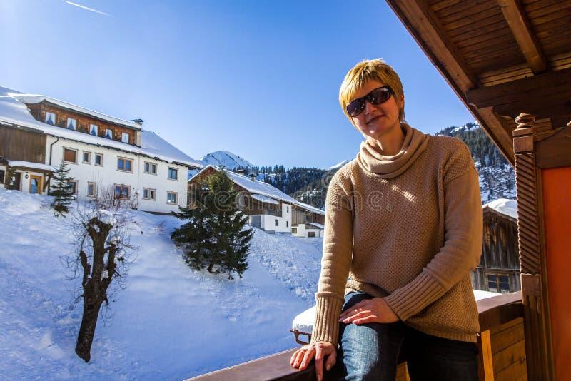 Jovem sentada na varanda de um hotel sob o sol brilhante do inverno imagens de stock