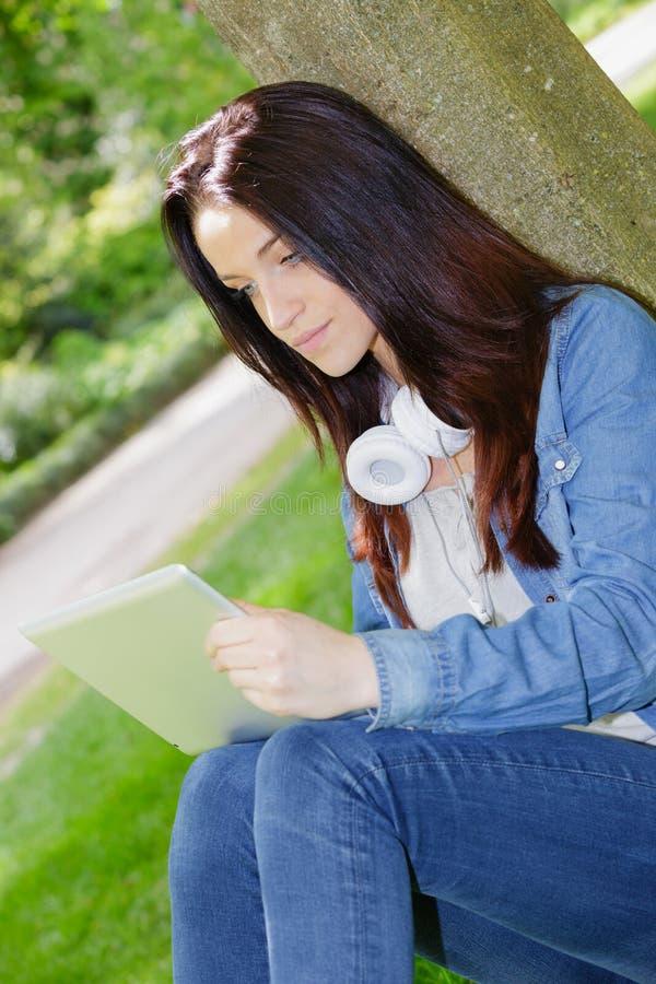 Jovem usando tablet no parque imagens de stock