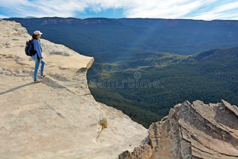 Joven adulta mirando el paisaje desde el Lincoln Rock Lookout al atardecer del Grose Valley ubicado dentro del Blue fotografía de archivo