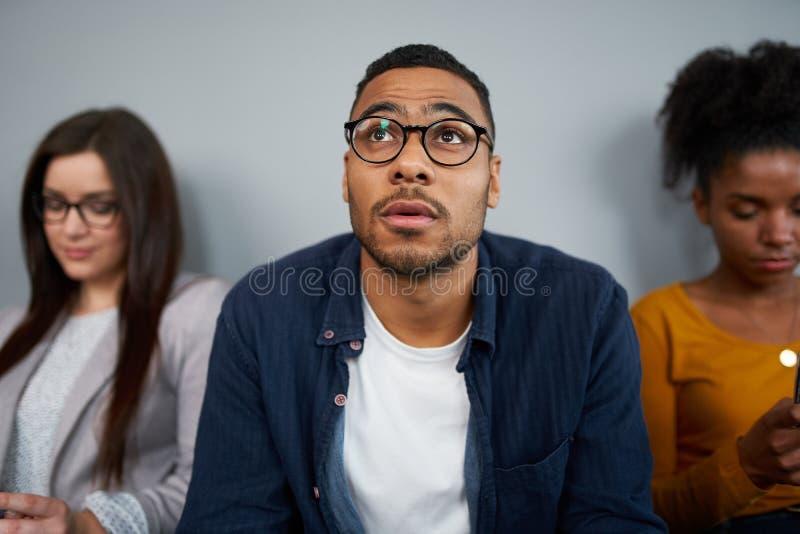 Joven afroamericano preocupado esperando su turno para entrevistarlo sentada con otras candidatas foto de archivo