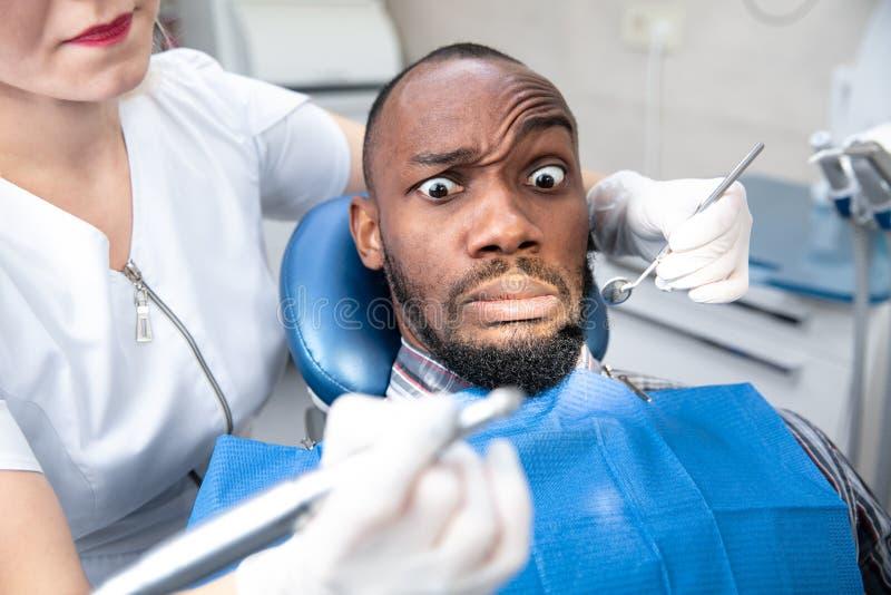 Joven afroamericano visitando la oficina del dentista, parece asustado foto de archivo libre de regalías