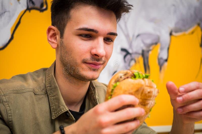 Joven antropófago una hamburguesa que lo sostiene con sus manos imagenes de archivo
