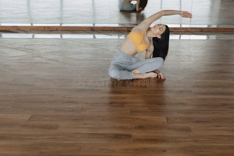 Joven atractiva en un suelo de madera haciendo yoga, estiramientos y relajantes fotografía de archivo libre de regalías